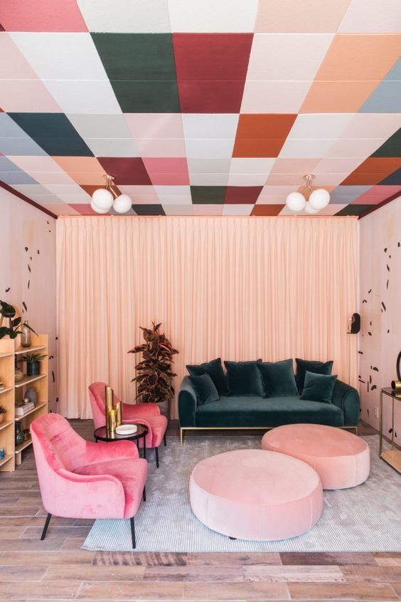 a bright living room with a printed colorful ceiling, a dark green sofa, bright pink chairs and light pink ottomans