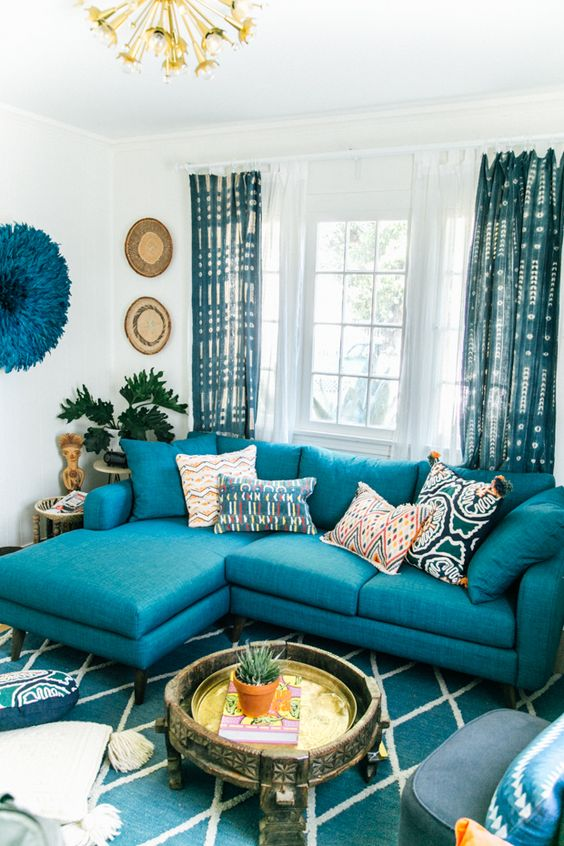 a bright living room with a turquoise sofa, a turquoise printed rug and curtains, decor on the wall and a carved wooden coffee table