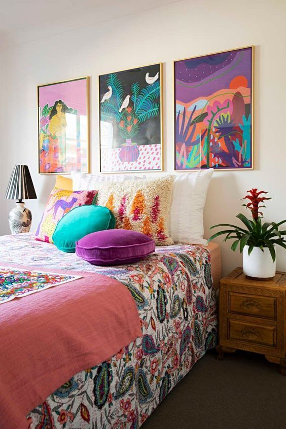 a bright maximalist bedroom with wooden furniture, a colorful gallery wall and bright textiles and bedding is amazing
