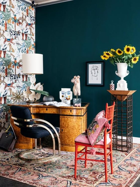 a bright maximalist home office wiht a teal and a wallpaper wall, a vintage desk, a navy chair and a red one, colorful textiles and a creative lamp