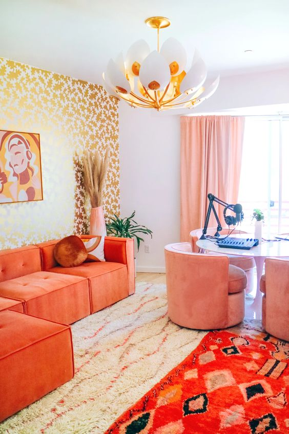 a bright maximalist home office with a gold stencild wall, a desk for several people, pink chairs, a coral sectional and bold rugs