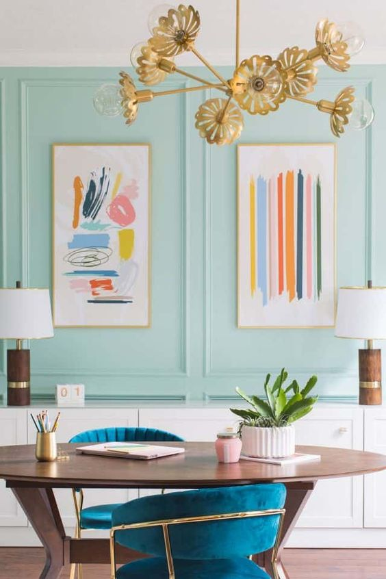 a bright maximalist home office with aqua panels, an oval desk and teal chairs, a gold floral chandelier and pretty artworks
