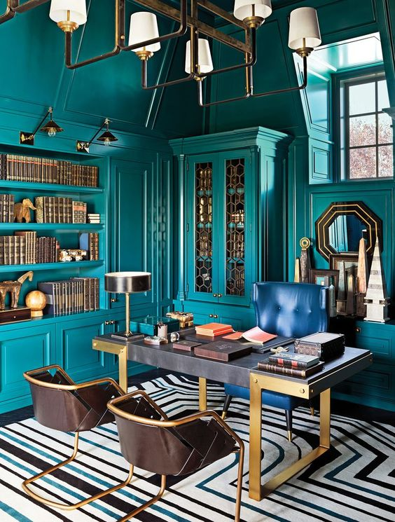 a bright maximalist home office with teal walls and matching built-in furniture and shelves, a refined desk, a navy and leather chairs, a chic chandelier