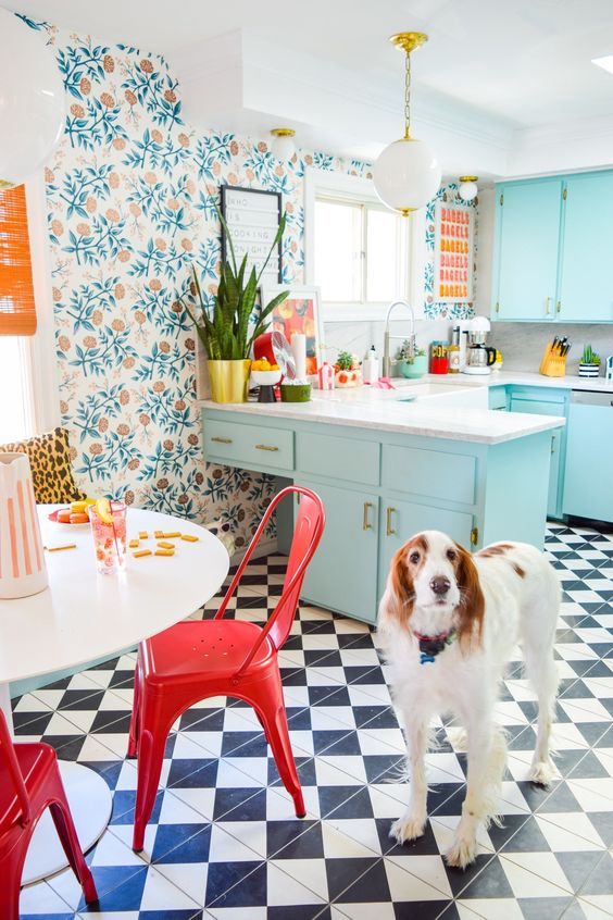a bright maximalist kitchen with botanical wallpaper, light blue cabinets, a white table and red chairs plus a checked floor