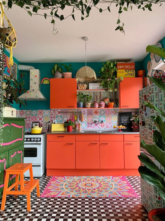 a bright maximalist kitchen with coral furniture, a bright floor and rug, a green wall and a colorful backsplash plus lots of potted plants
