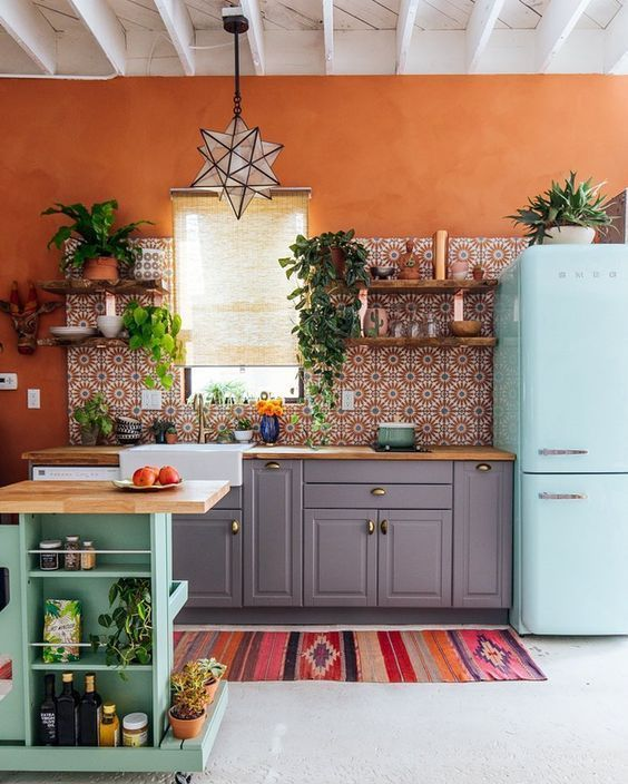 a bright maximalist kitchen with grey cabinets, an aqua-colored kitchen island and a matching fridge, rust walls and bright tiles