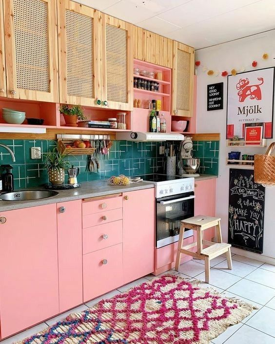 a bright maximalist kitchen with rattan and pink cabinets, a green tile backsplash, a bright printed rug and colorful art