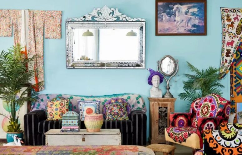 a bright maximalist living room with blue walls, colorful furniture, bright pillows and bold curtains is a crazy and very eclectic space