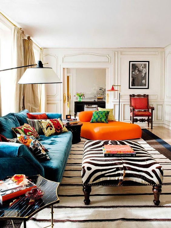 a bright maximalist living room with neutral paneled walls, a teal sofa and an orange lounger, a zebra ottoman, colorful pillows and rugs
