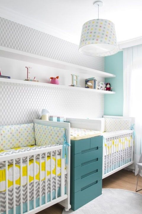 a bright twin nursery with an accent wall, white cribs, a teal changing table with storage, a pendant lamp and a shelf for display