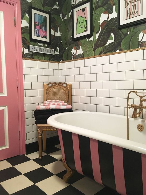 a brigth bathroom with white subway tiles, tropical leaf wallpaper, a striped bathtub, a pink door and a checked floor plus pop artworks