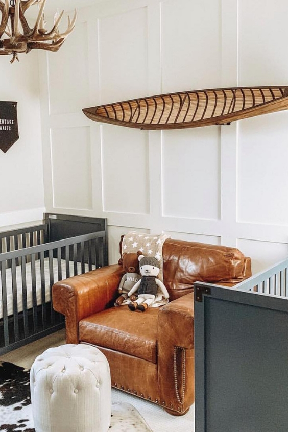 a catchy adventurous twin nursery with grey cribs, a leather chair, a canoe, an antler chandelier and white paneled walls
