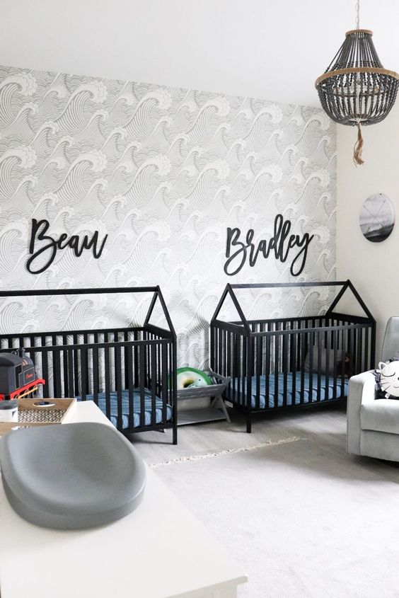 a catchy twin nursery with black cribs, an accent wall, a wodoen bead chandelier and a cool changing table is lovely