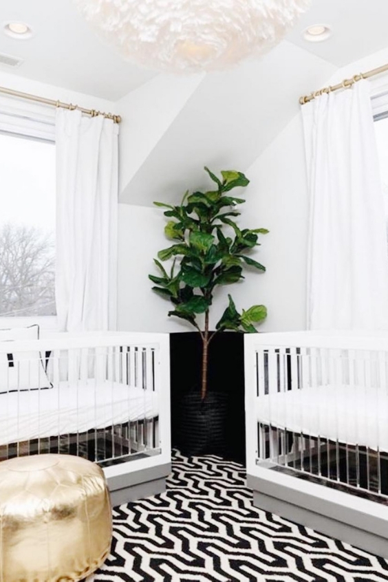 a chic contemporary nursery with acrylic cribs, white curtains, a bold geo rug and a gold ottoman plus a faux statement plant