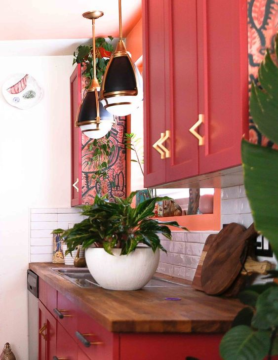 a chic maximalist kitchen with red cabinetry, butcherblock countertops, retro pendant lamps and lots of potted plants