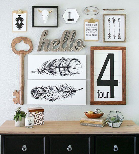 a chic mid century modern gallery wall with a rustic feel   signs, a wooden key, some artworks and calligraphy is chic