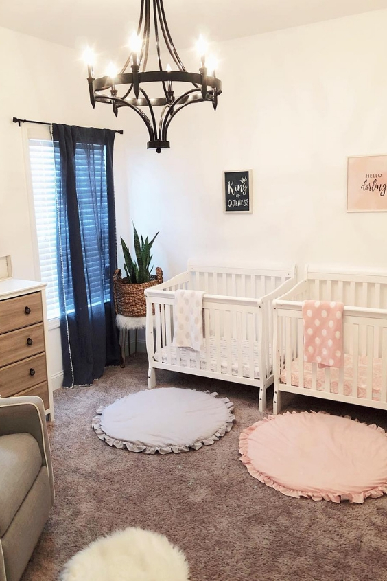 a chic nursery with white walls and white and grey furniture, layered rugs, a metal chandelier, a navy curtain and some potted plants