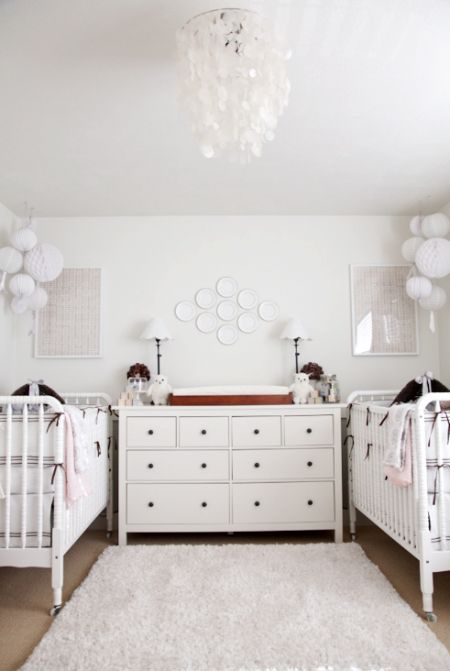 a chic twin nursery in white, with white furniture, neutral artworks, a mother of pearl chandelier and lovely bedding