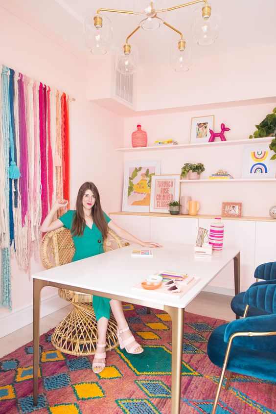 a colorful fancy home office with pink walls, open shelves and a large storage unit, a large desk, a peacock chair, navy chairs and colorful fringe