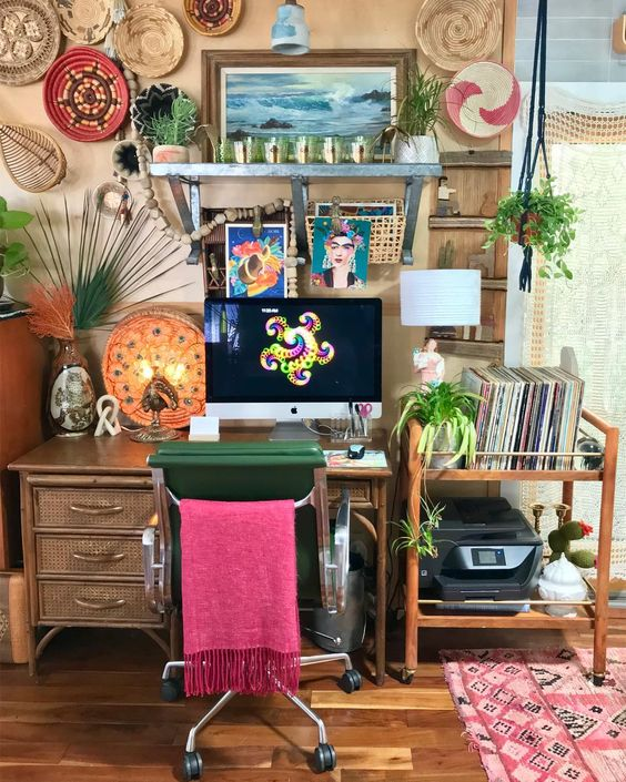 a colorful home office with tan walls, a rattan desk and a cart, colorful decorative baskets and a boho rug plus a pink chair cover