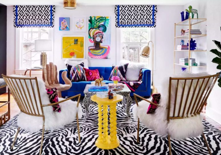 a colorful living room with a bold printed rug and curtains, an electric blue sofa and a yellow table, super bright pillows and a gallery wall
