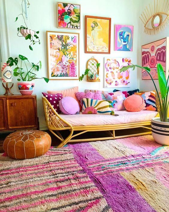 a colorful living room with bright rugs, a bright gallery wall, a colorful sofa with pillows and potted plants