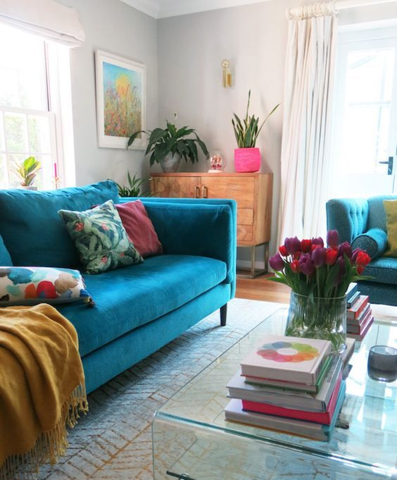 a colorful living room with dove grey walls, a turquoise sofa, bright pillows and accessories, an acrylic coffee table and bold blooms
