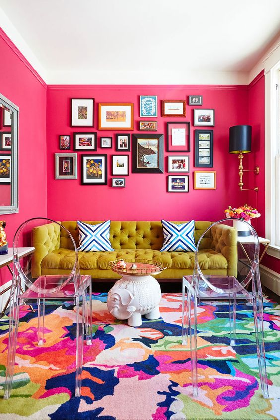a colorful living room with hot pink walls, a mustard sofa, a colorful rug, acrylic chairs and an elegant gallery wall