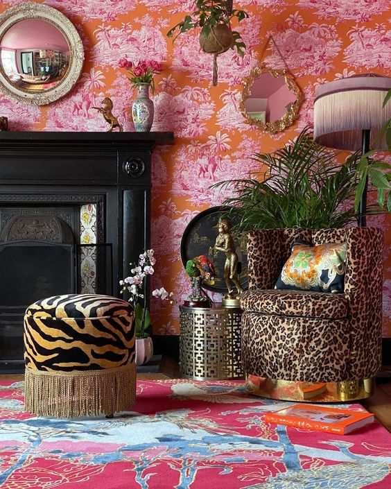 a colorful living room with pink and red wallpaper, a red and blue rug, a fireplace, a leopard print chair and a zebra ottoman