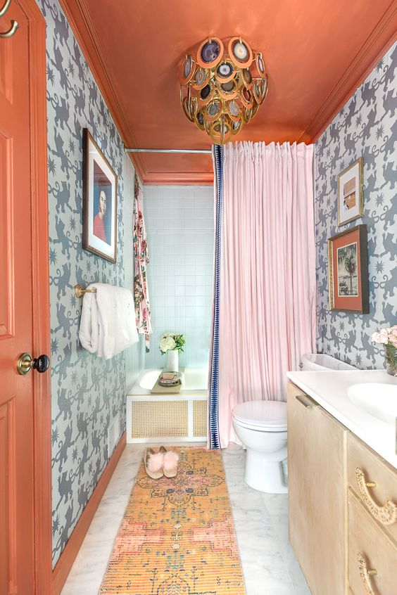 a colorful maximalist bathroom with grey printed walls, a rust ceiling and a door, a bold rug, a creative agate chandelier and a pink curtain