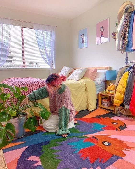 a colorful maximalist bedroom with a bold rug, a bright gallery wall, pastel bedding and colorful curtains plus a potted plant