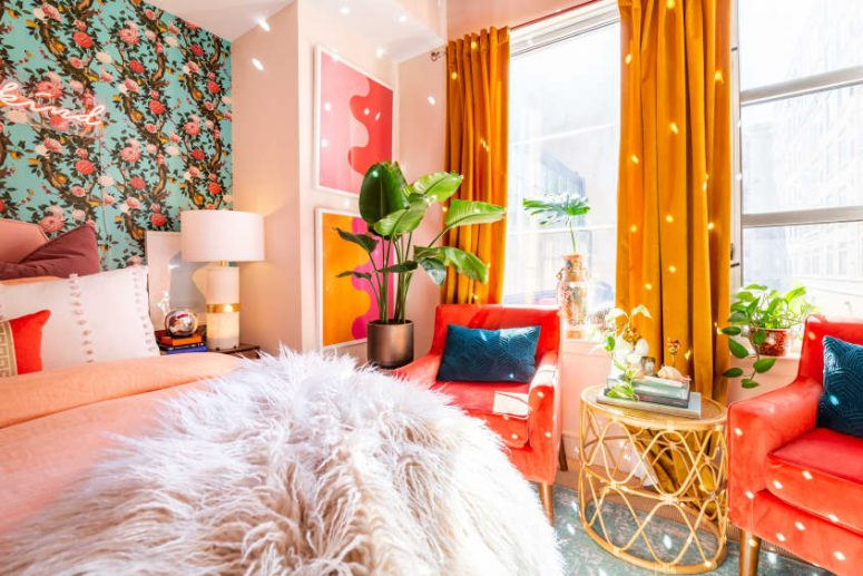 a colorful maximalist bedroom with a floral accent wall, a red chair and mustard curtains, a disco ball and a neon light plus bright bedding