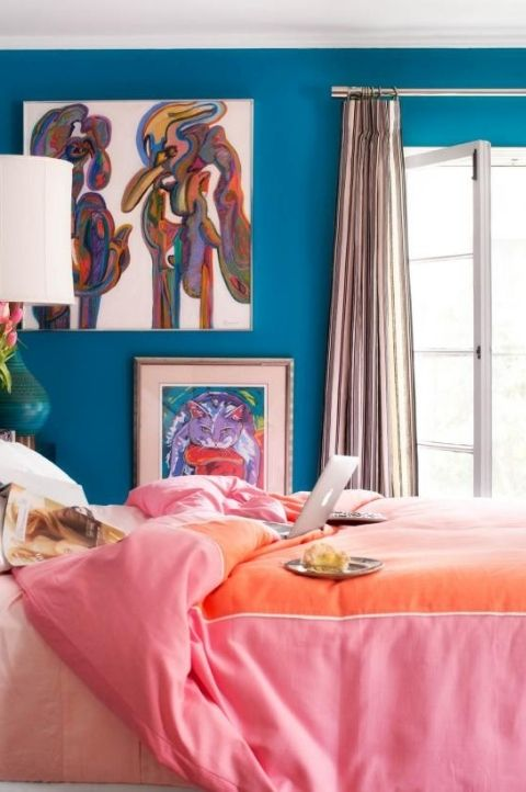 a colorful maximalist bedroom with blue walls, bright artworks, colorful bedding and curtains plus a green table lamp