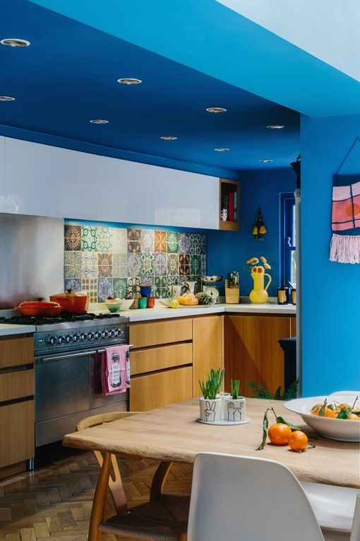 a colorful maximalist kitchen with bold blue walls and a ceiling, white and stained cabinets, white countertops and a colorful backsplash