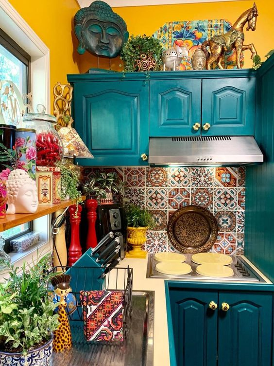 a colorful maximalist kitchen with mustard walls, teal cabinets, colorful tiles on the backsplash and lots of accessories and potted plants