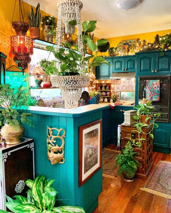 a colorful maximalist kitchen with yellow walls, emerald cabinets, a colorful tile backsplash and lots of potted plants