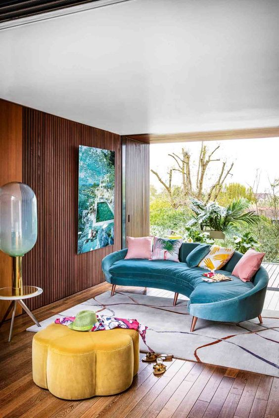 a colorful maximalist living room with a blue curved sofa, a yellow flower-shaped ottoman, a bright artwork and colorful printed pillows