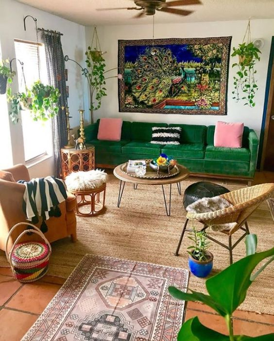 a colorful maximalist living room with a tile floor, a green sofa and rattan furniture, colorful pillows and rugs and potted plants