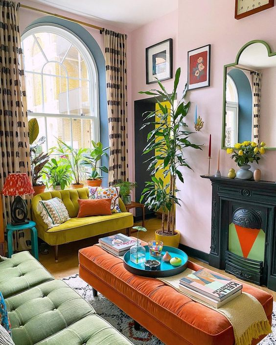 a colorful maximalist living room with bright furniture, a non-working fireplace, statement plants, printed curtains and pillows