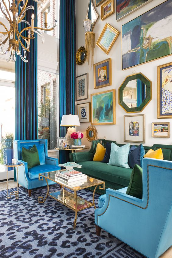 a colorful maximalist living room with double height ceilings, a neutral floor with a printed rug, blue and green furniture, a bold gallery wall