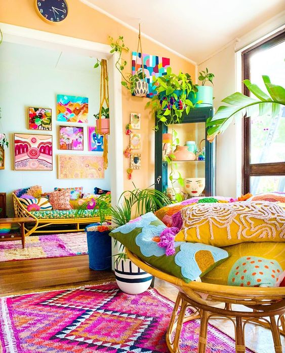 a colorful maximalist space with rattan furniture, colorful accessories and textiles plus bright gallery walls is super fun
