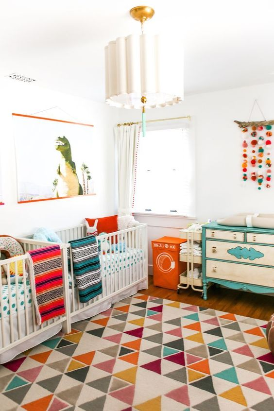 a colorful mid-century modern nursery with white cribs, a neutral and turquoise dresser, colorful bedding and a colorful rug plus a cool chandelier