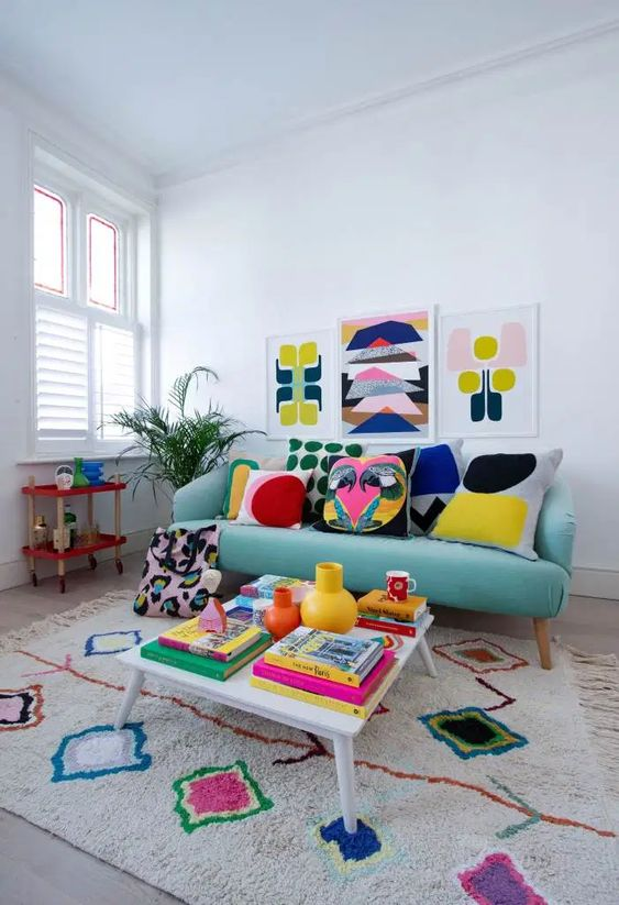a colorful retro-inspired living room with a turquoise sofa, a colorful rug, a gallery wall, pillows and books fill the space with bright colors