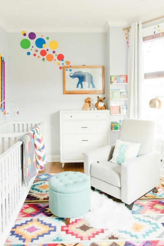 a colorful twin nursery with two white cribs, a dresser, a white chair and a turquoise ottoman, colorful textiles and decor