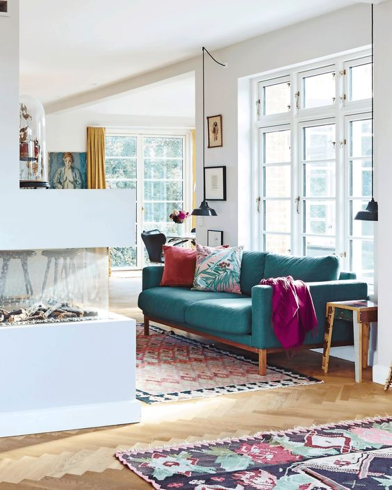 a contemporary living room with a fireplace, a turquoise sofa and bright textiles, pendant lamps and printed mini rugs
