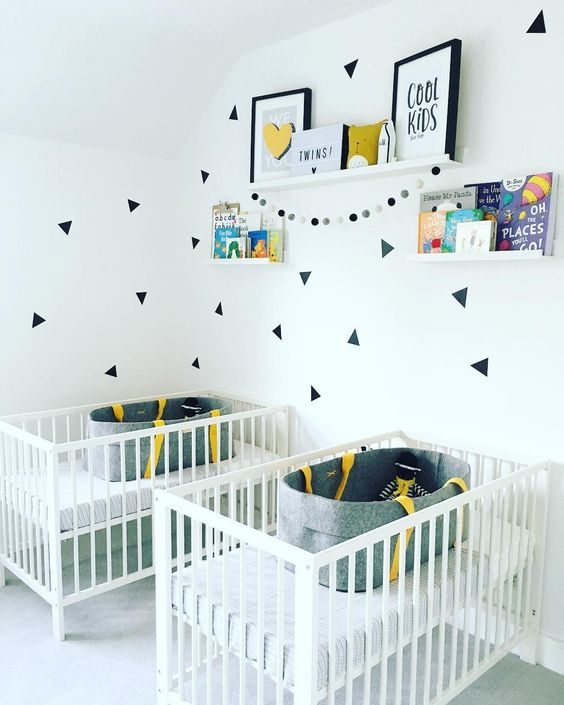a contemporary twin nursery with white cribs, shelves with art and books and catchy decals for an accent