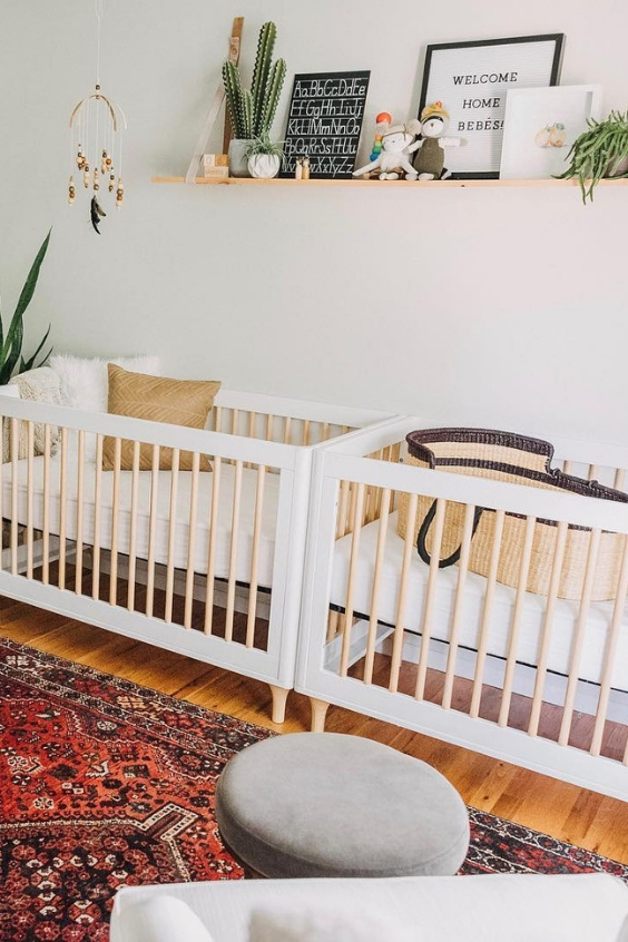 a cool boho twin nursery with white cribs, a Persian rug, a grey chair with a footrest, a shelf with some pretty pieces