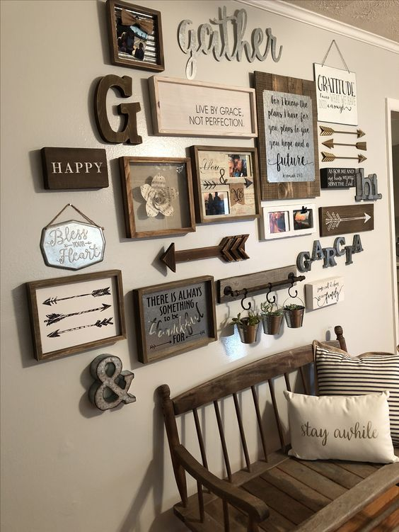 a cool vintage rustic gallery wall with arrows, monograms, various artworks and signs in frames, greenery in buckets