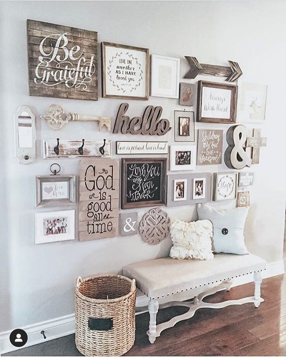 a cozy rustic gallery wall including a wooden arrow, a key, a calligraphy piece, wooden signs and some photos in stained wooden frames