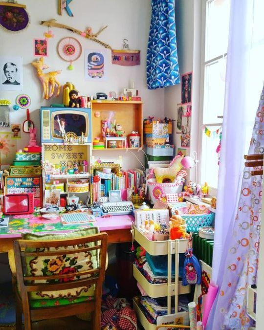 a crazily boho maximalist home office with a hot pink desk, a green chair, colorful textiles, accessories and decor is amazing